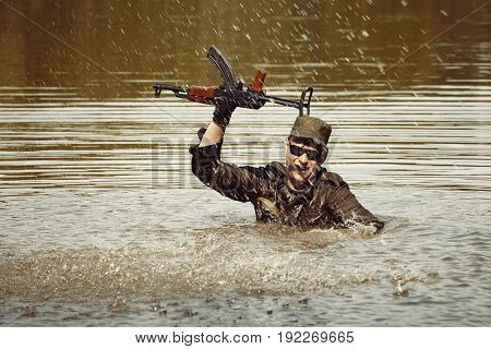 Soldier in uniform swimming in lake with assault rifle