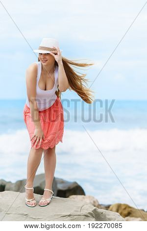 young pretty european girl seductively looking to the camera on background of blue calm sea at sunny summer day