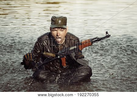 Crazy soldier in uniform sitting in lake with assault rifle