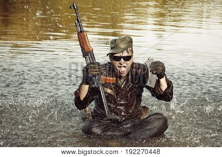 Wet and dirty soldier in uniform overcomes river with assault rifle