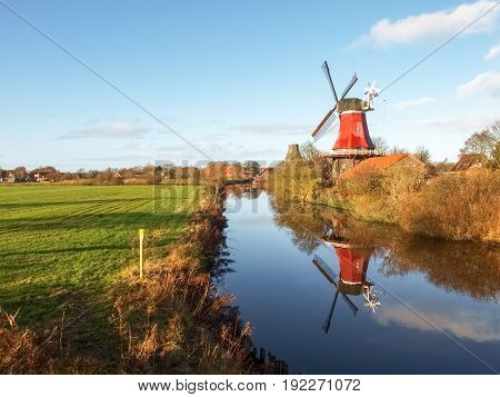 Greetsiel, Germany - December 6, 2014: Traditional Windmill working and still used to grind. The second mill is currently under renovation due to a violent hurricane.
