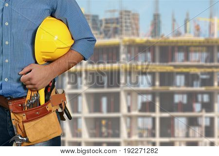 Male worker with yellow hardhat and tools against blurred background of building under construction.