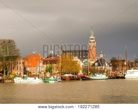 Leer, Germany - December 8, 2014: Views of the touristic harbor and the traditional boats moored. Typical houses in the background of the North Sea.