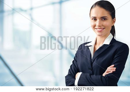 Young adult businesswoman in a suit on a light background with copy space.