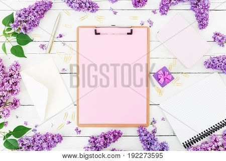 Freelancer or blogger composition. Minimalistic workspace with clipboard, envelope, pen, box, lilac and accessories on white background. Flat lay, top view.