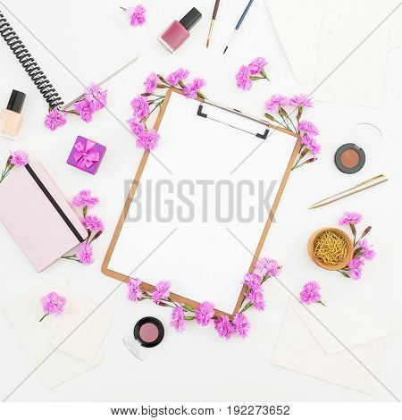 Blogger or freelancer workspace with clipboard, notebook, pink flowers and accessories on white background. Flat lay, top view.