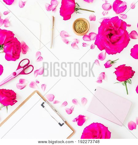 Workspace with pink roses, petals and clipboard, notebook and accessories on white background. Flat lay, top view.
