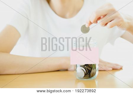 Woman hands with coins in glass jar close up