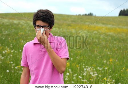 Allergic Boy With Glasses And Pink T-shirt Blows His Nose
