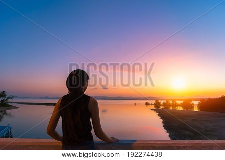 Asian young woman enjoy and happiness beautiful view of sunrise sky on topical beach Thailand