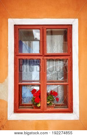 Closed Old Window With Red Flowers In Orange Wall