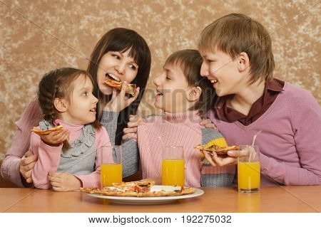 Portrait of mother with children eating pizza
