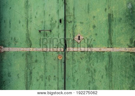 Closed up of aged vintage green door with keyhole as background.