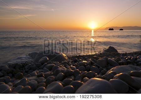 Landscape with the sun the sea and pebbles beach. Sunrise