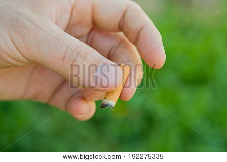 Cigarette in the man's hand on a background of green grass blur. The concept of a healthy lifestyle, the dangers of Smoking