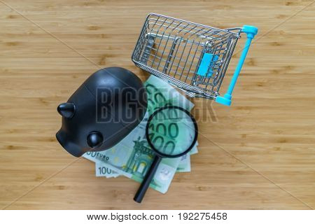 Selective focus on black piggy bank and miniature shopping cart with magnifying glass and pile of Euro banknotes on wood table.