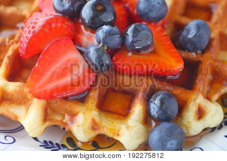 Closeup of a homemade waffle with fresh strawberries and blueberries with syrup