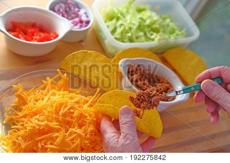 A man makes tacos at home with taco shells ground beef lettuce onions tomatoes and grated cheese