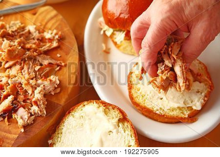 A man puts homemade pulled chicken on a brioche bun