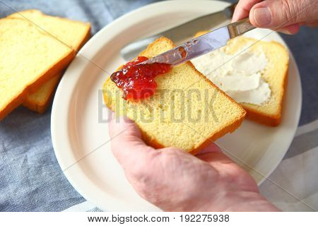 An older man makes a cream cheese and strawberry jam sandwich point of view