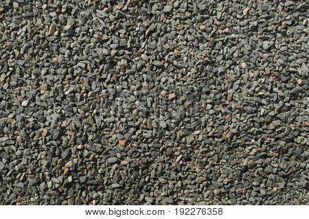 Background of small gray macadam fragments texture