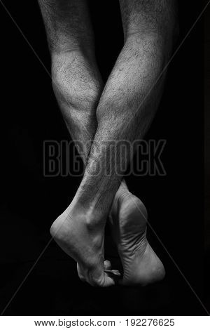 Naked Muscular Male Legs On A Black Background