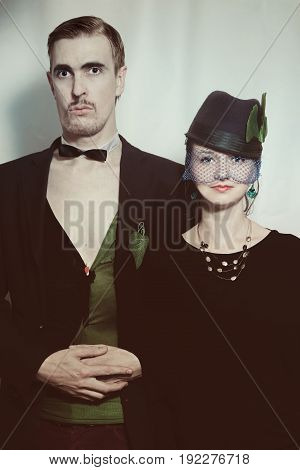 Young couple theater actors in a retro style on a light background. Vintage