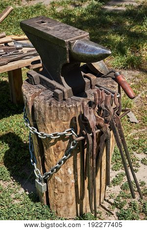 Anvil on a wooden log blacksmith ladle chain and ladle for coal