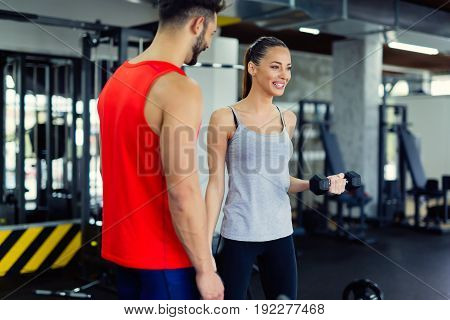 Young adult woman working out in gym doing biceps with trainer