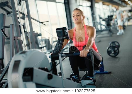 Young cute woman doing exercises with rowing machine in gym