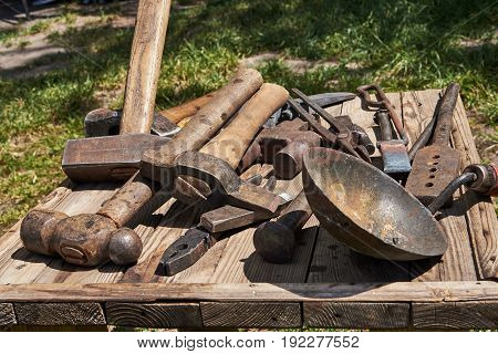 On the table are tools for the blacksmith (hammers forceps chisels coal ladle)