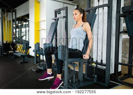 Young attractive woman exercising on machine in gym leg workout