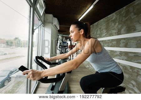 Young beautiful woman doing indoor biking exercise alone