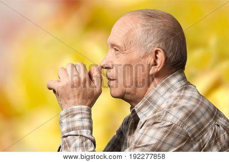 Elderly sad old senior man with grey hair against a yellwo background.