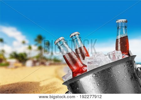 Cold bottles of beer in an ice bucket on a sunny beach.