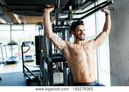 Young bodybuilder training in gym on machine shoulder exercise