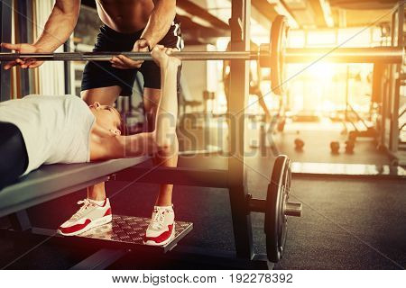 Cute young woman doing bench press with personal trainer in gym