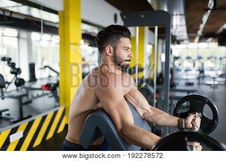 Athlete muscular bodybuilder in ym training biceps with bar