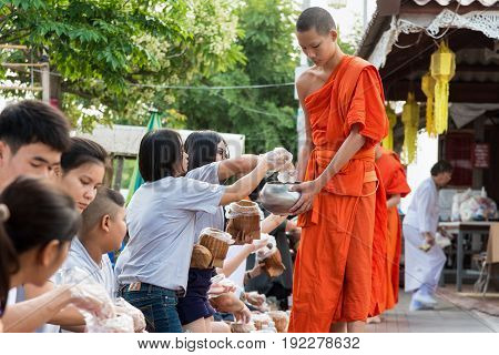 PHAYAO THAILAND-OCTOBER 24 2016: Mother daughter and thai buddhists are making merit with offer sticky rice and food to monk bowl in the morning OCTOBER 24 2016 in Thailand