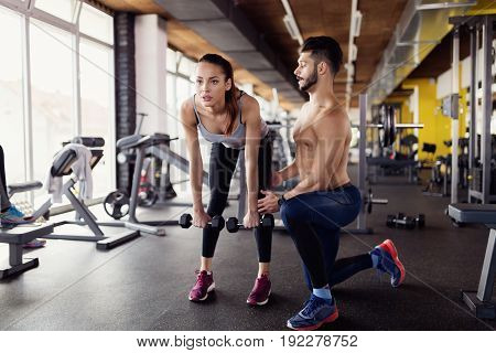 Young attractive woman doing lunge exercise in gym with trainer