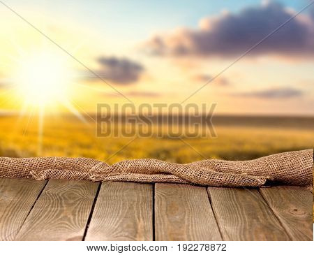 Background design of burlap sack on a empty wooden table and sunset background.
