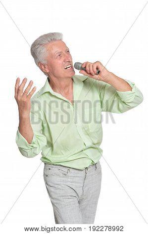 Portrait of senior man singing karaoke isolated on white background