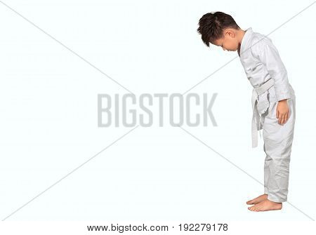 Little Asian boy doing karate on a white background.