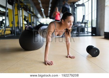 Young attractive woman exercising with swiss ball in gym