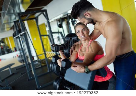 Beautiful girl doing exercises in gym with personal trainer