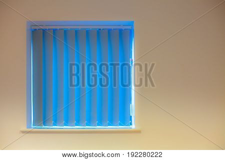 Modern interior design. Blue vertical blinds over window on yellow cream painted wall. Soft image with copy space.