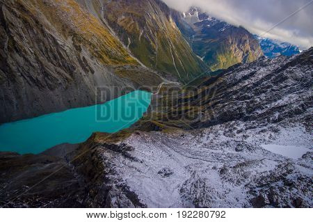 Beautiful landscape and turquoise lagoon, mighty mountains covered by snow behind, South Island in New Zealand.