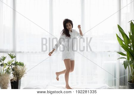 Asian woman Beautiful young smiling and jumps on his bed after waking