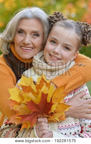 pretty little girl having fun with grandmother in autumnal park