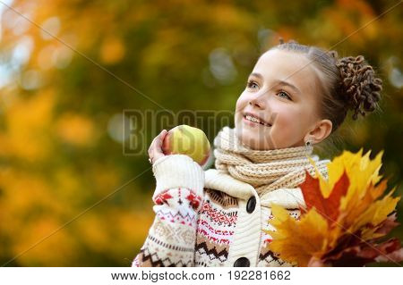 portrait of pretty little girl in autumnal park